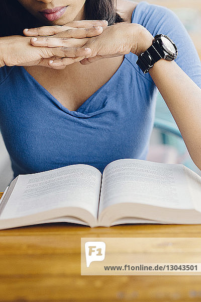 Midsection of woman with hands clasped sitting with book at sidewalk cafe