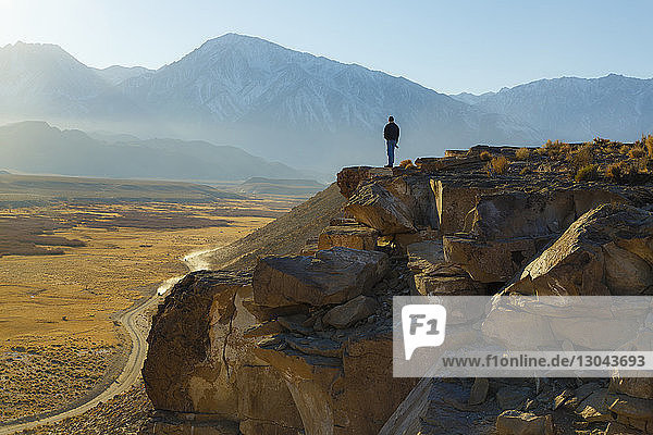 Rear view of man standing on rock formations against sky