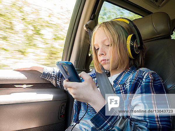 Boy using mobile phone while listening music in car