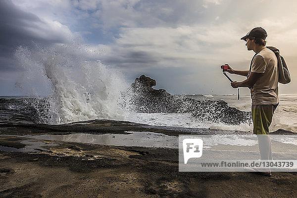Seitenansicht eines Mannes  der am Strand stehend vor bewölktem Himmel fotografiert