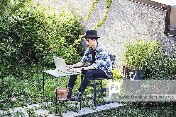 Mann mit Laptop auf der Terrasse