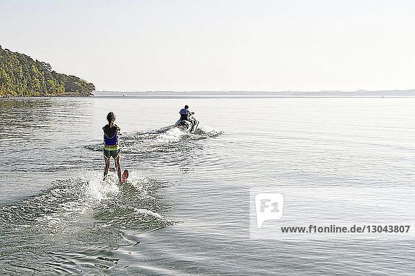 Rückansicht einer Frau beim Wakesurfen,  während ein Mann bei klarem Himmel auf einem See Boot fährt