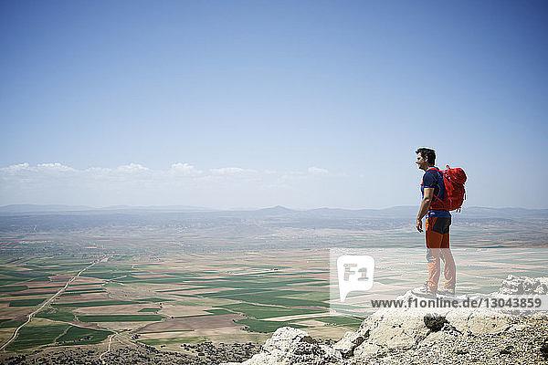 Seitenansicht eines Mannes mit Rucksack  der am sonnigen Tag auf einem Berg gegen den Himmel steht