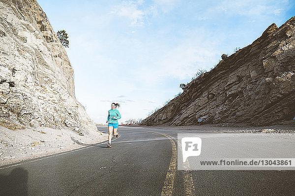 Sportlerin läuft in voller Länge auf Landstraße inmitten von Bergen gegen den Himmel