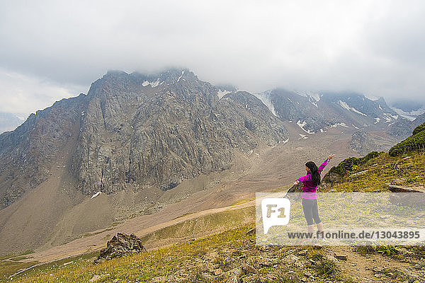 Hochwinkelaufnahme einer glücklichen Frau mit ausgestreckten Armen  die auf einem Berg steht