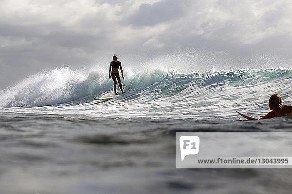 Wasserspiegel von Freunden beim Surfen im Meer vor bewölktem Himmel