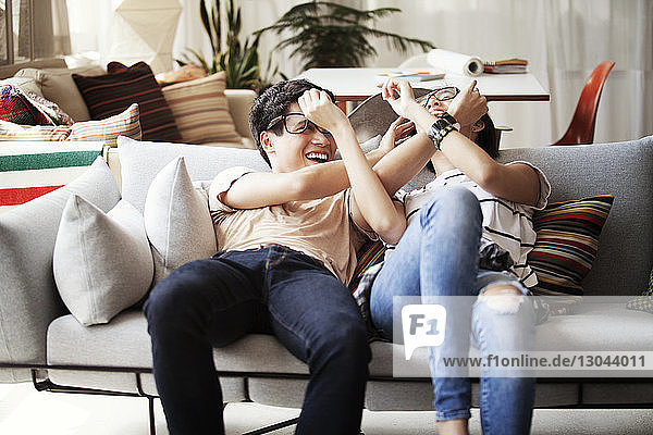 Verspieltes multiethnisches Paar  das zu Hause auf dem Sofa liegt
