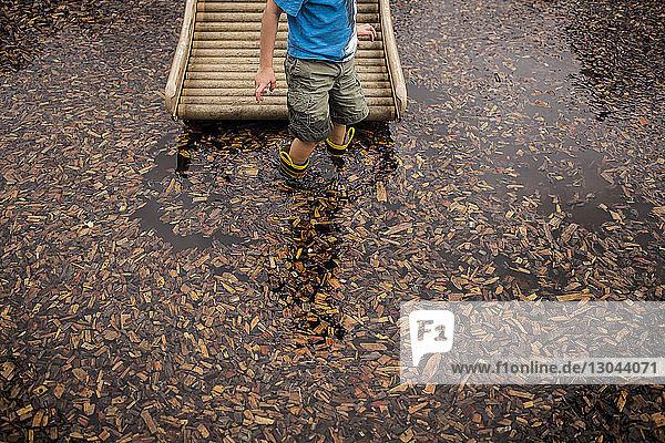Mitschnitt eines Jungen  der in einem mit Blättern bedeckten See steht
