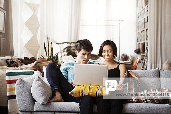 Young couple using laptop while sitting on sofa at home