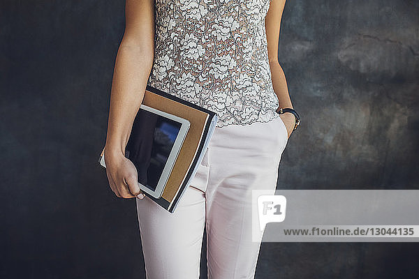 Midsection of businesswoman holding tablet and files while standing against wall at home office