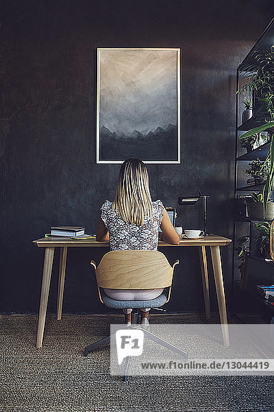 Rear view of businesswoman working while sitting at table in home office