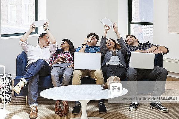 Glückliche Geschäftsleute,  die im kreativen Büro über Tablet-Computer Selbstgespräche führen