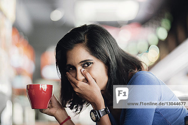 Portrait of happy woman covering mouth while holding coffee cup at sidewalk cafe