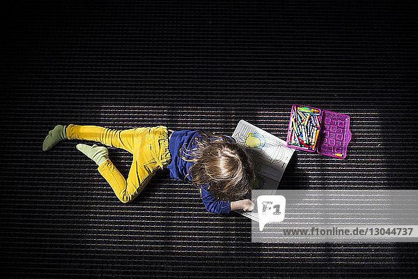 High angle view of girl drawing on book while lying on bed
