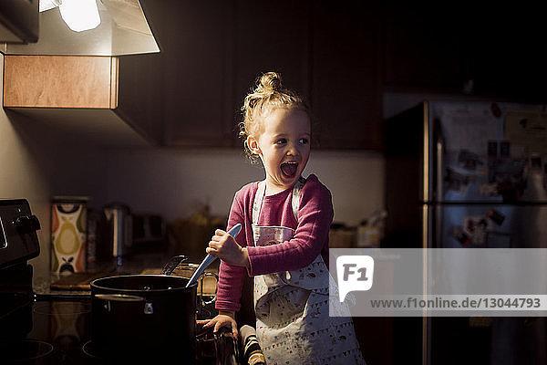 Glückliches Mädchen schaut weg  während es zu Hause in der Küche Essen zubereitet