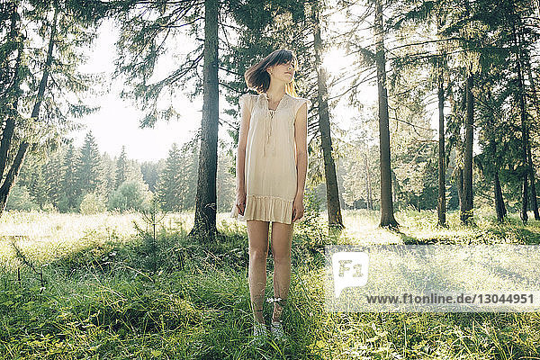 Full length of young woman standing on grassy field in forest