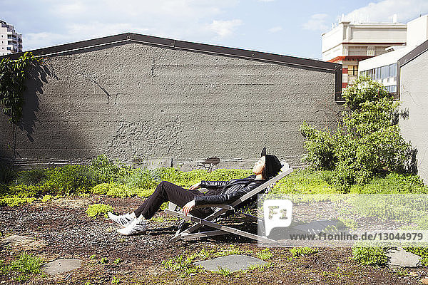 Seitenansicht einer Frau  die sich auf einem Liegestuhl auf der Terrasse entspannt