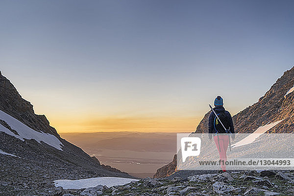Rückansicht einer Wanderin  die bei Sonnenuntergang auf einem Berg gegen den Himmel steht