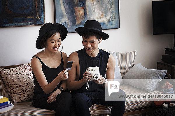 Glücklicher Mann hält Sofortbildkamera  während er ein Foto mit einer Frau im Wohnzimmer betrachtet