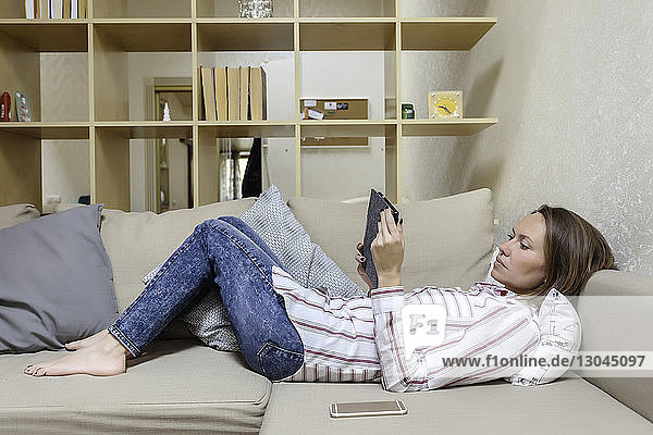 Side view of woman using tablet computer while lying on sofa at home