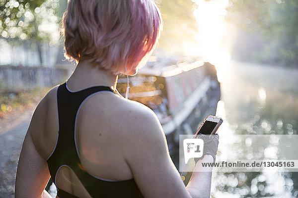 Frau mit Smartphone am See im Park