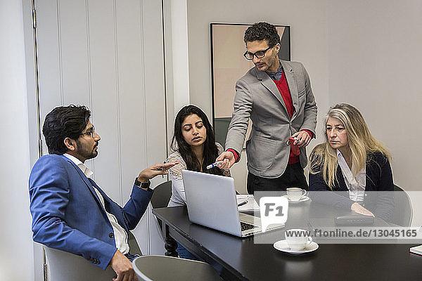Geschäftsleute diskutieren über Laptop-Computer am Schreibtisch im Büro