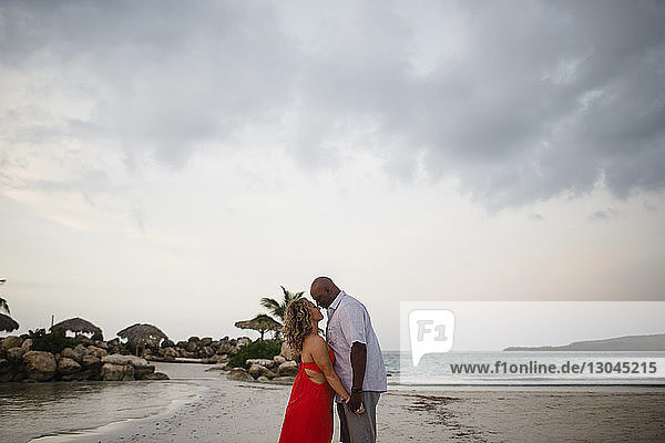 Side view of couple standing face to face at beach against cloudy sky