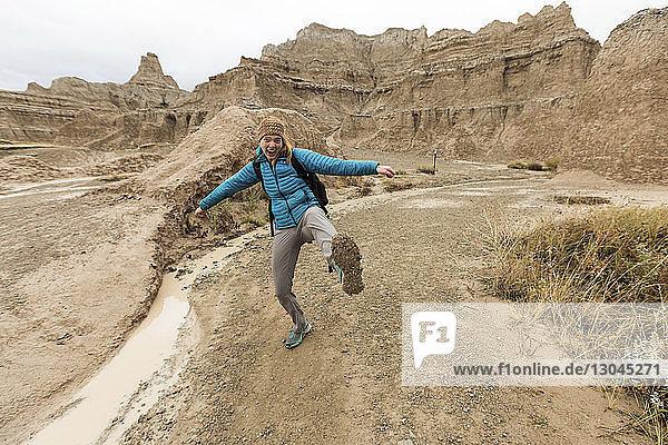 Porträt einer glücklichen Frau  die auf dem Feld gegen Felsformationen im Badlands-Nationalpark tanzt