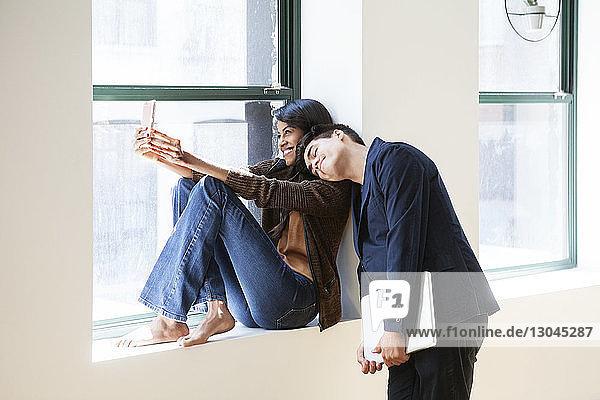 Fröhliche Geschäftsfrau nimmt Selfie mit Kollegen  die im Kreativbüro auf der Schulter schlafen