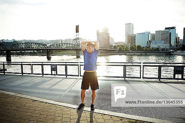 Sporty man exercising on promenade in city