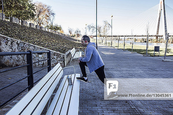 Side view of man exercising on bench at park