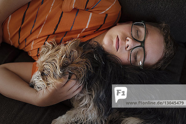 Schrägansicht eines Jungen mit zu Hause schlafendem Yorkshire Terrier Schrägansicht eines Jungen mit zu Hause schlafendem Yorkshire Terrier