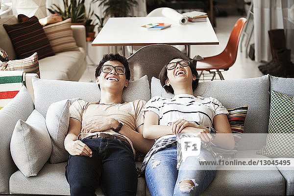 Fröhliches Paar liegt zu Hause auf dem Sofa