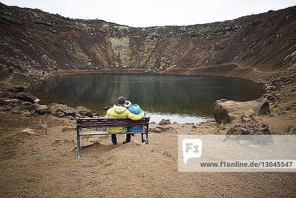 Rückansicht eines Paares  das auf einer Bank sitzt und auf den Teich schaut