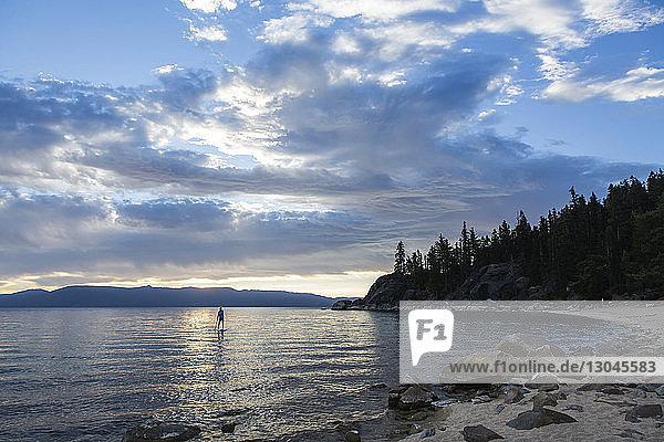 Fernblick eines Mannes beim Paddeln auf einem See vor bewölktem Himmel