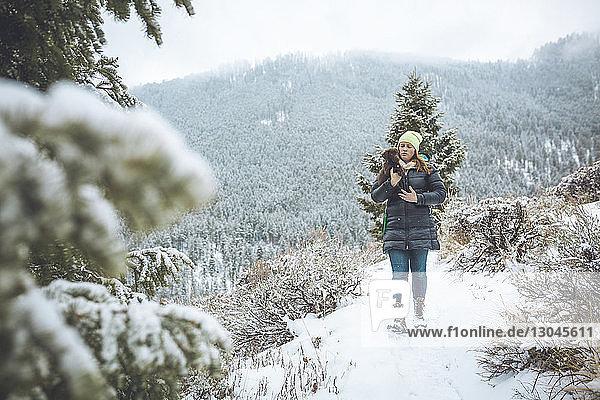 Frau  die einen Welpen trägt  während sie auf schneebedecktem Feld geht