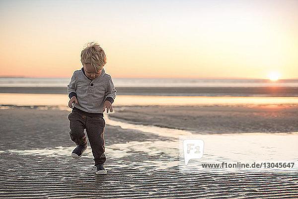 Junge in voller Länge  der bei Sonnenuntergang am Strand gegen den Himmel läuft