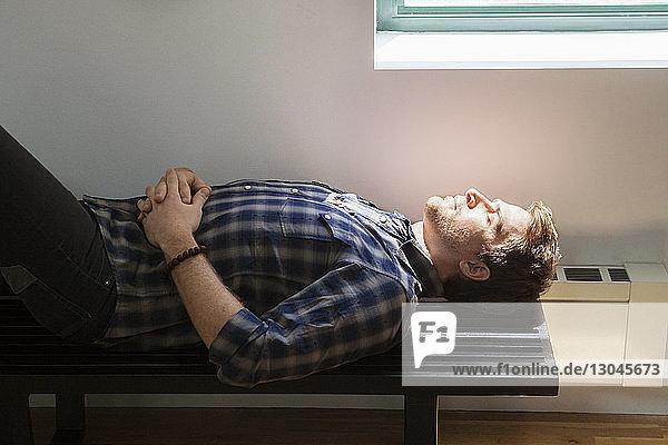 Seitenansicht eines auf einer Bank schlafenden Geschäftsmannes im Kreativbüro Seitenansicht eines auf einer Bank schlafenden Geschäftsmannes im Kreativbüro