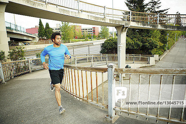 Männlicher Athlet joggt auf der Brücke