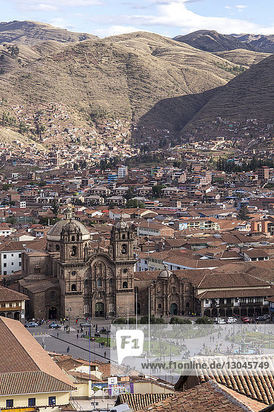 High angle view of cathedral amidst houses against mountains in city