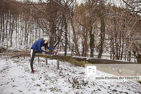Woman stretching leg on pole in forest during winter