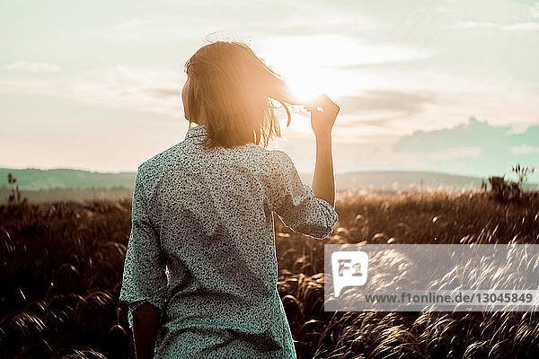 Rückansicht einer Frau  die Haare hält  während sie bei Sonnenuntergang auf dem Feld gegen den Himmel steht