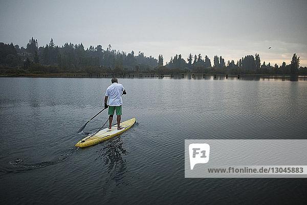 Full length of senior man paddleboarding on lake during sunset