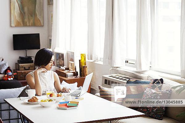 Junge Frau benutzt Laptop zu Hause