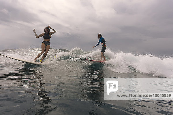 Freunde surfen auf dem Meer gegen bewölkten Himmel