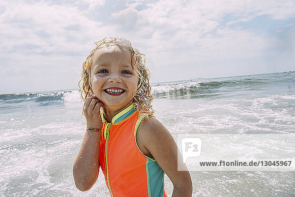 Happy girl standing at beach against cloudy sky