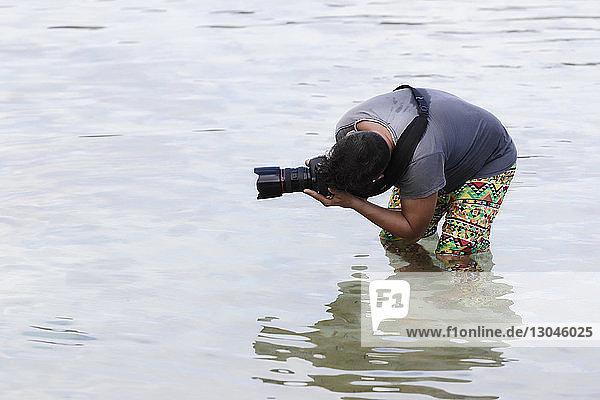 Mann fotografiert im Meer stehend