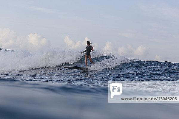 Frau surft auf Wellen im Meer gegen den Himmel