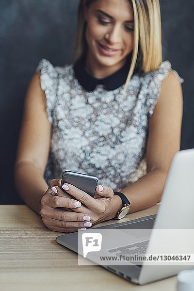 Businesswoman using mobile phone at table in home office