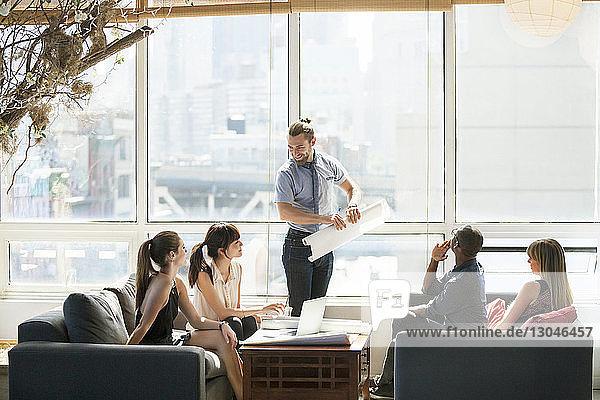 Geschäftsmann hält Blaupause bei Treffen mit Kollegen